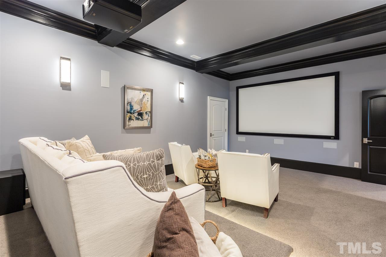The media room is located in the finished basement and features tiered flooring, crystal sconces, overhead movie projector and associated components which will convey, programmed lighting via remote, and access to the full kitchen.