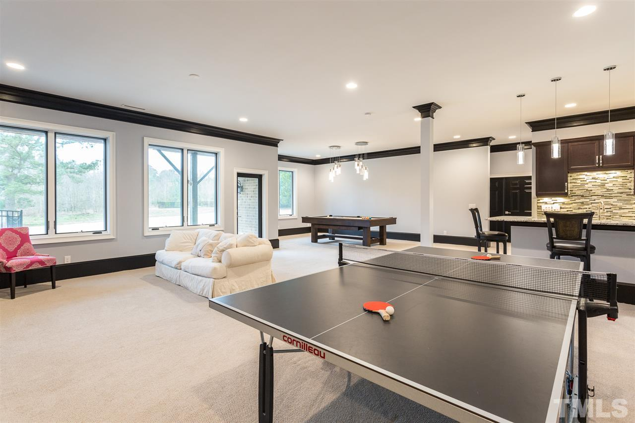 Located in the finished basement, the exercise room features a floor mat for comfort, crown molding, ceiling fan, recessed lights and a large storage closet.