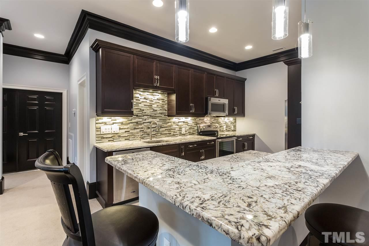 Granite counters, under cabinet lighting, tile backsplash, and stainless appliances including refrigerator,dishwasher, and microwave. Open to the basement entertainment areas and the media room.