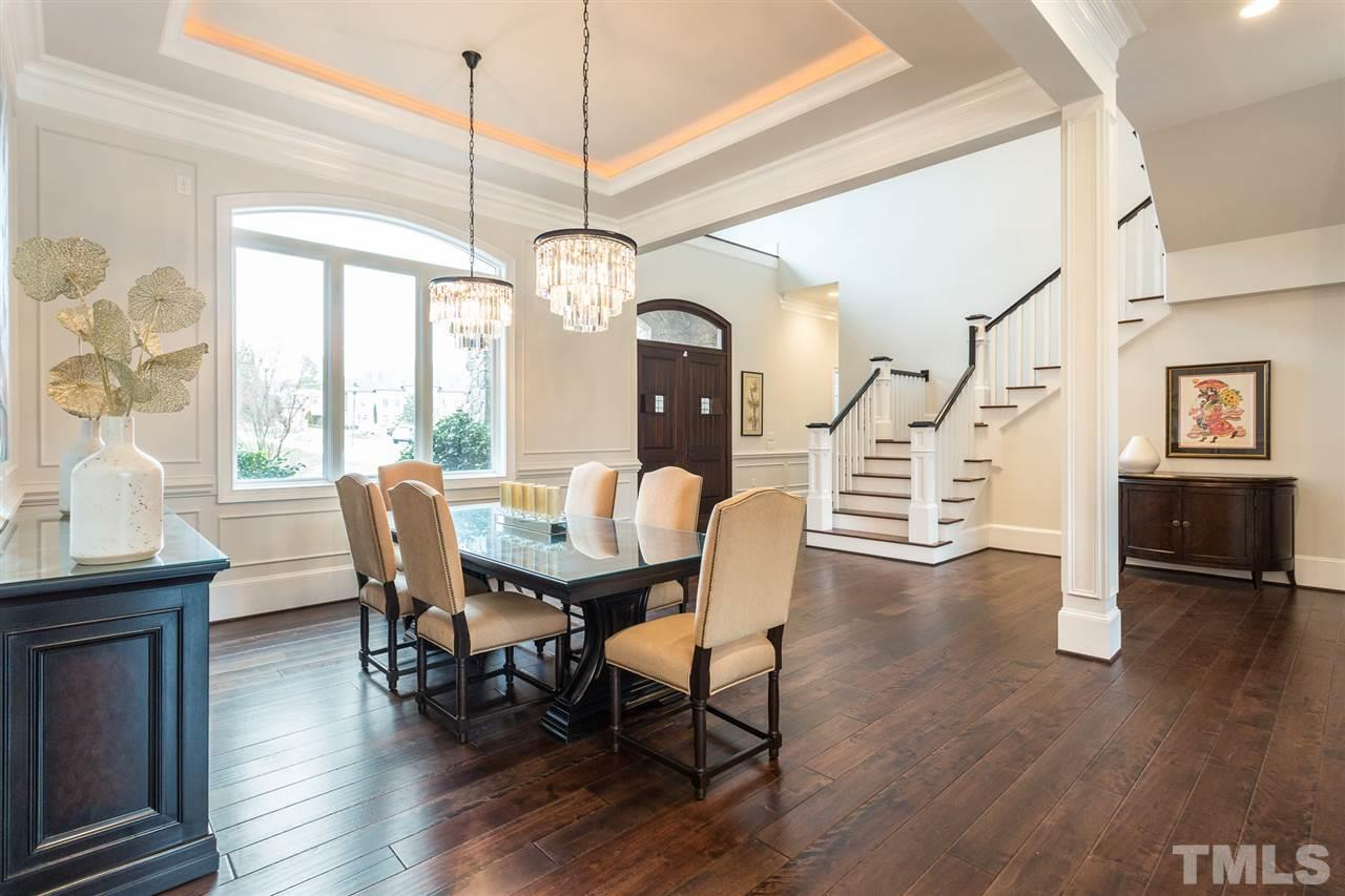 The elegant dining room is open to the family room and offers a tray ceiling with ambient lighting, crown molding, wainscoting, hardwood floors, and  majestic twin crystal chandeliers.