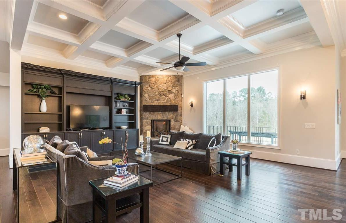 The family room is graced with a coffered ceiling and features a custom built-in bookcase with an opening for a large flat screen TV, gas fireplace with stone surround, ceiling fan and hardwood floors.