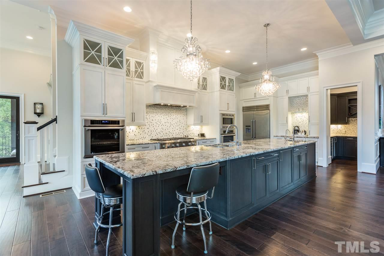 Long central island w/granite countertops provides 2 sinks including access to filtered drinking water. The gas range offers 6 burners and a griddle. Floor to ceiling cabinets with glass accent doors. Tile backsplash and under cabinet lighting.