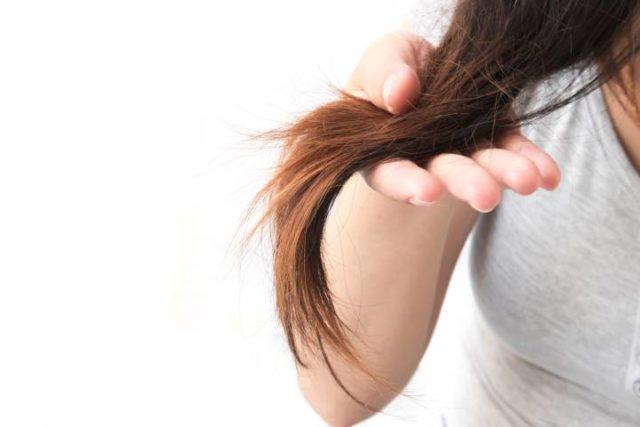 Mão feminina segurando mecha de cabelo danificado
