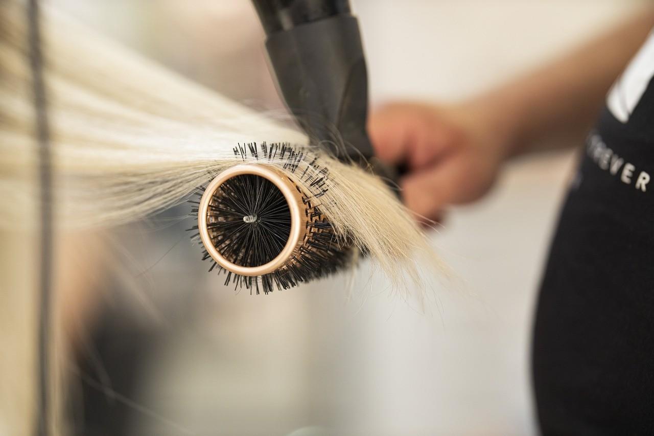Profissional secando mecha de cabelo loiro descolorido