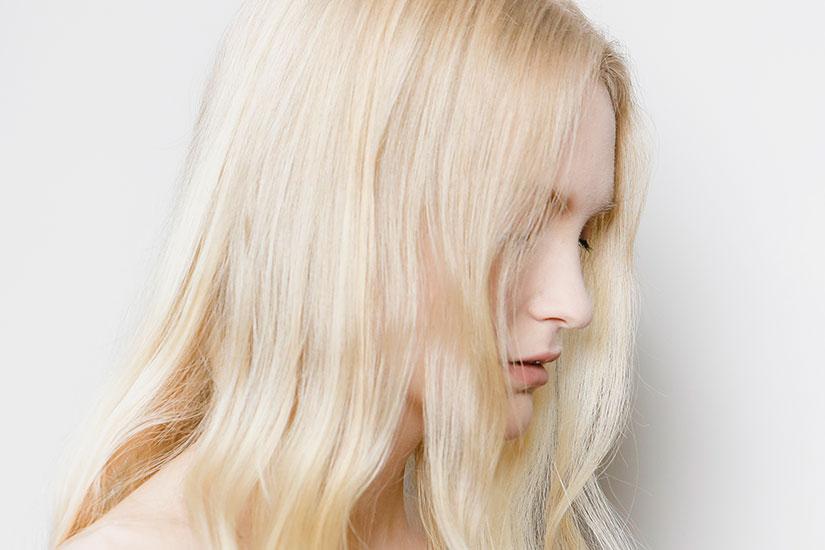 Menina de perfil com cabelo loiro claríssimo descolorido, sem danos