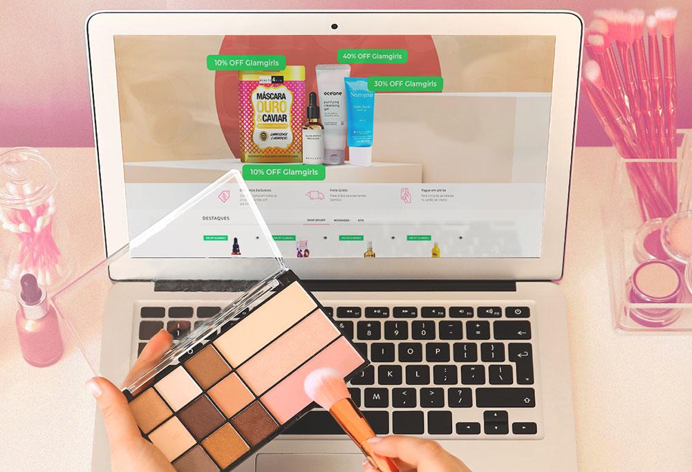 um notebook ao fundo e uma mão segurando um kit de maquiagem