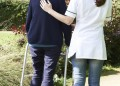 Carer Helping Senior Woman To Walk In Garden Using Walking Frame