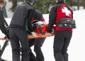 Two ski patrol and two paramedics transporting injured skier to sled.