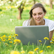 Woman watching Bible Study Video Session on Computer in a Field