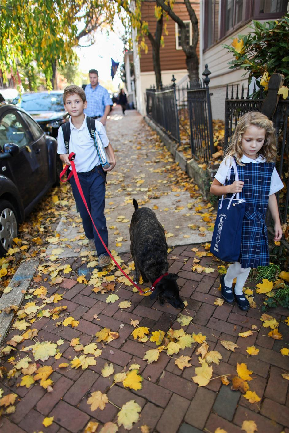 Children walking home from school with dog