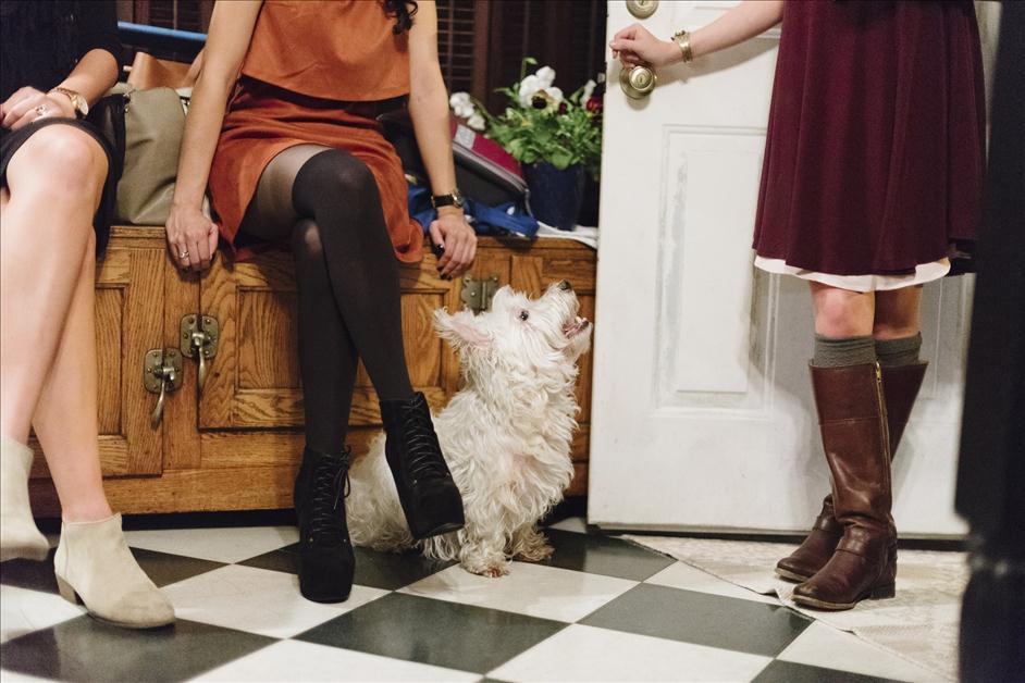 Girls sitting cross-legged in kitchen with white dog