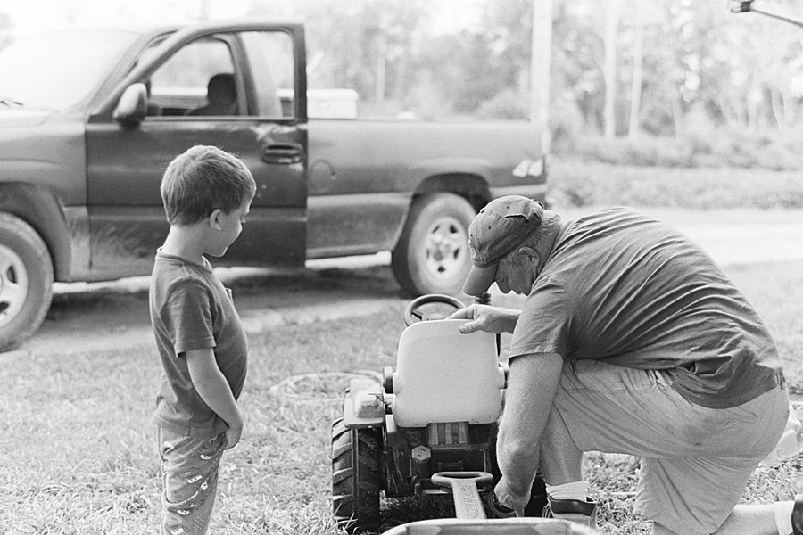Boy with father fixing tractor on the farm