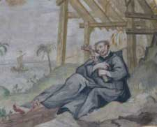 St. Francis Xavier sitting under a rough shelter, embracing a crucifix
