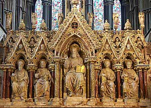 Detail inside a church, tan and gold statue of five men seated in niches, one larger and more imposing than the others, probably St. Egwin.