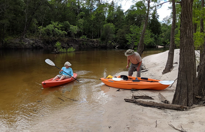 An Image of an elderly couple in kayaks on the bank of the Perdido River trip