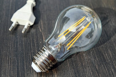 A Close up of a light bulb resting on a wodden table with a white power plug that can be seen in the background