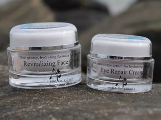 An image of the eye & face cream 2 container set from Orkan18 displayed on a rocky beach