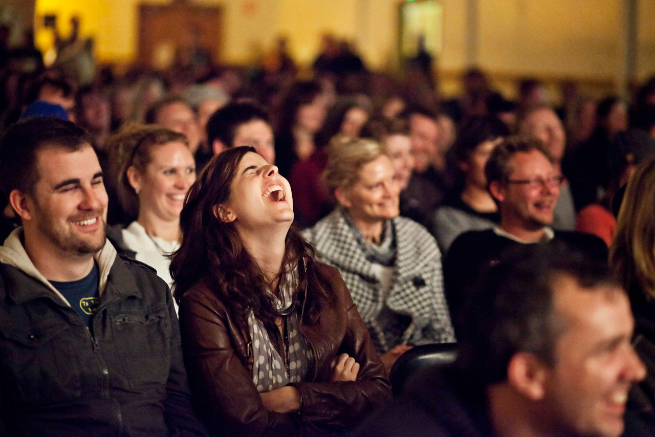 An image of a woman in the audience with her head tilted back laughing hysterically.