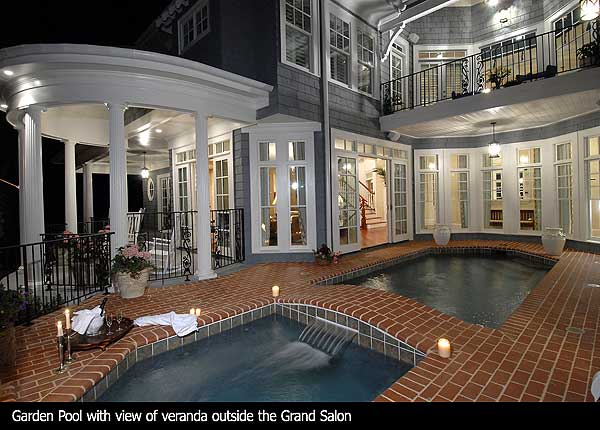 Red brick patio wrapping around backyard swimming pool and hot tub