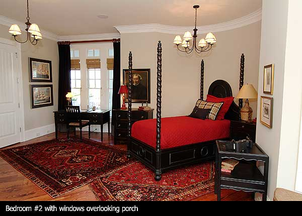 Second bedroom with white walls, hard wood floor, rugs and antique furniture