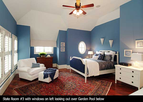 Guest bedroom with wood floor, large rug, blue walls and white furniture with ceiling fan