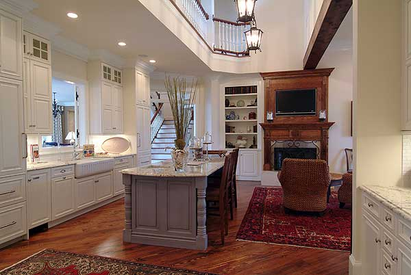 Kitchen with white cabinets and grey island opening up into sitting room