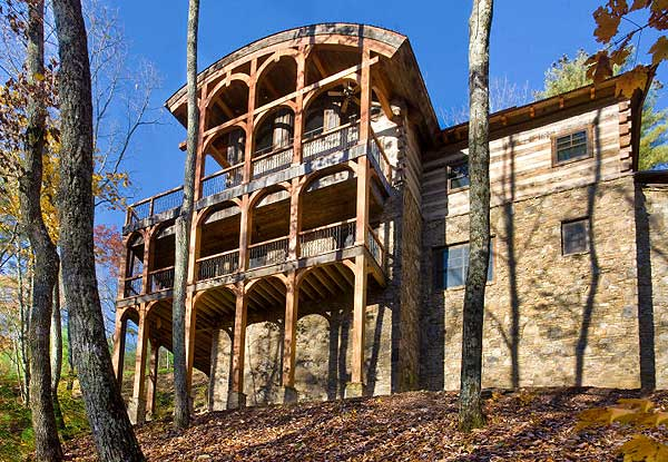 Rear view of mountain log home on the edge of a ravine. The home boasts 3 floors and 2 decks.