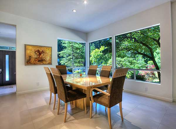Dining room overlooking heavily treed backyard with white walls and tile flooring