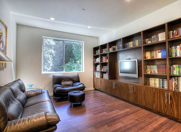 Library and media room with wood flooring, floor-to-ceiling bookshelves and leather furniture