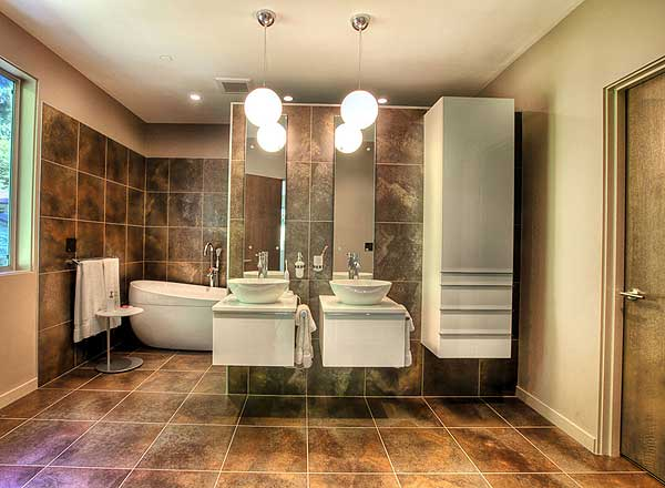 Luxury master bathroom with double vanity, freestanding tub and extensive brown tile-work