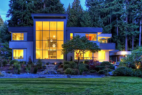 Night-time view of illuminated modern 2-story home with brightly lit great room