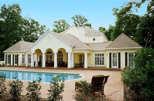 Backyard swimming pool and brick patio of luxury contemporary plantation home surrounded by trees