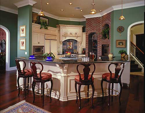 Spectacular kitchen design in green, white and some use of brick. Kitchen includes bar stools at eat-in counter.