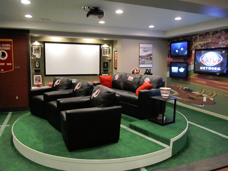 Sports-themed home theater and man cave with round stadium seating, recliners and black sofa