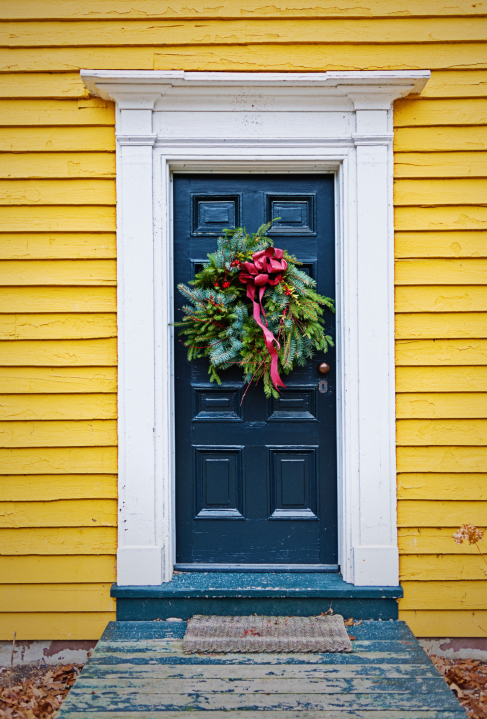 Blue door with white frame as entry for yellow home