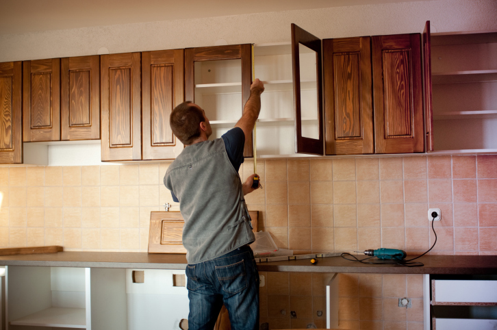 Custom cabinet installer installing open-faced wood kitchen cabinets
