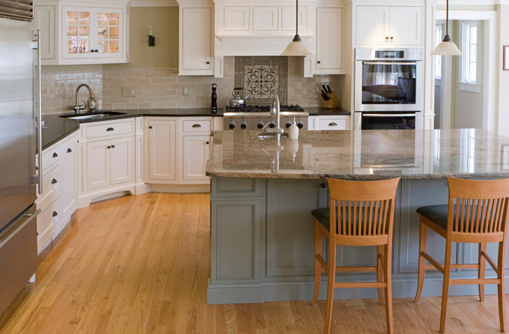 Large White Kitchen With Grey Island And Light Hard Wood Floors Designed  With Contemporary Hardwar