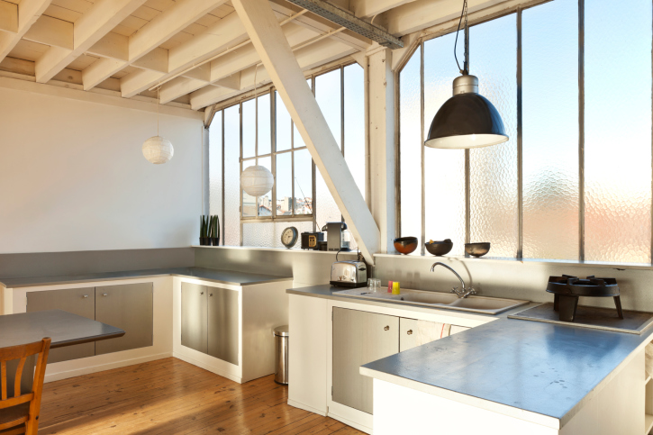 Bright airy kitchen with large hanging pendant light and 2 white round pendant lights
