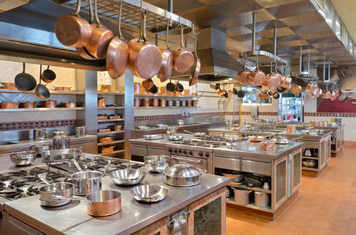 Large commercial kitchen with copper pots hanging from a series of pot racks