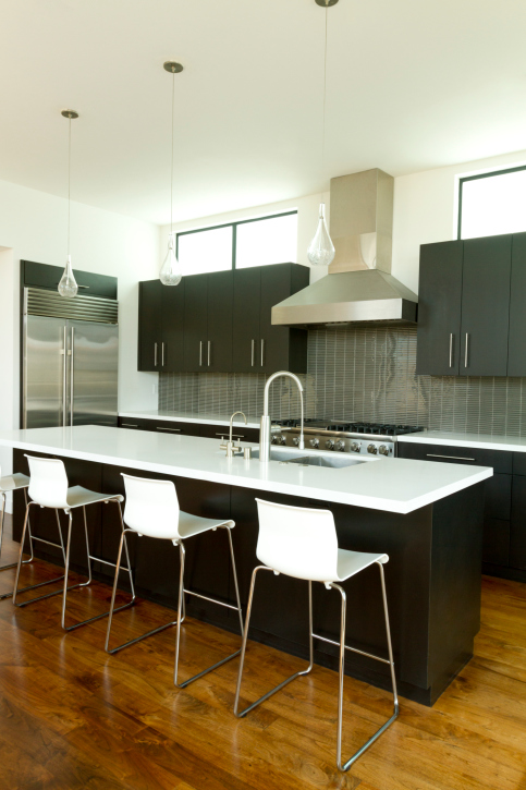 Black and white kitchen with 3 white bar stools lined up to the kitchen island