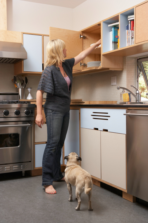 Woman in kitchen that has open-faced shelving used for storing cookbooks and recipes