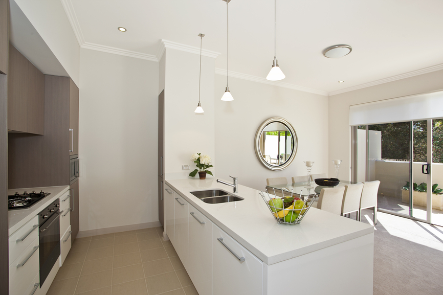 White kitchen with 3 silver pendant lights from white ceiling