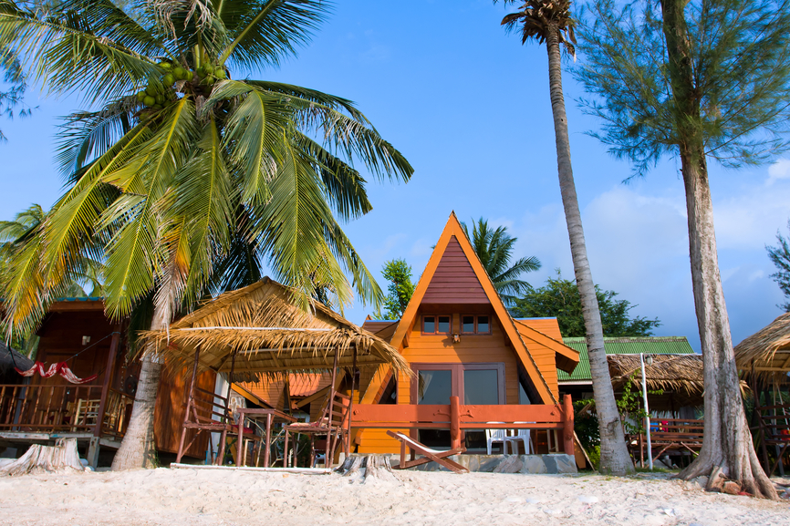 Classic A-frame home on a sandy beach with palm trees