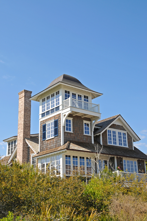 Grey shingle style beach house with lookout tower and white framed windows