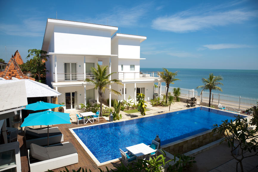 White villa on beach with large swimming pool