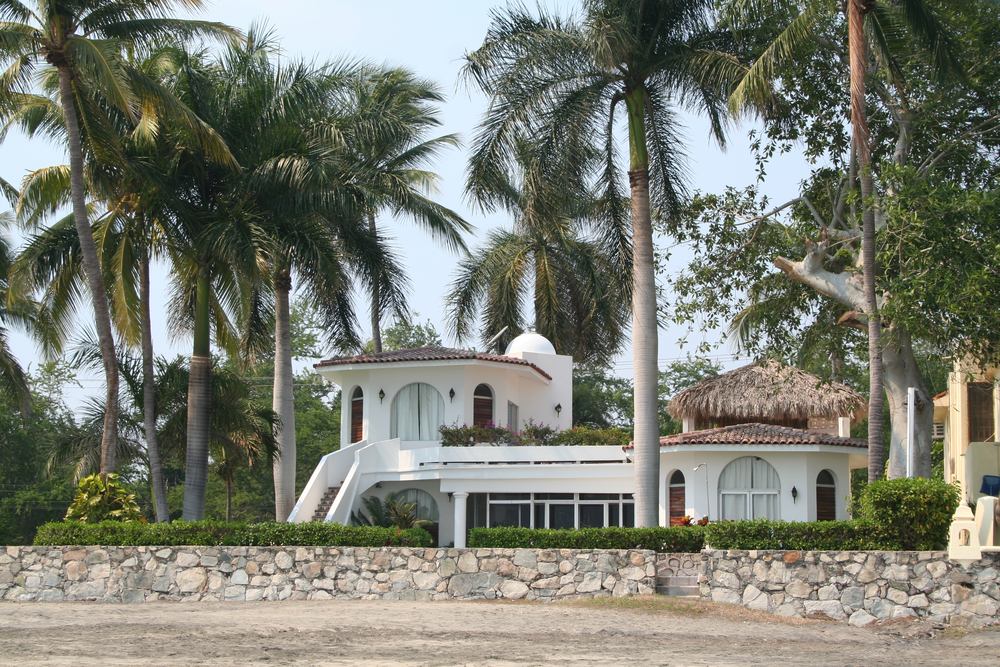 White beach home on large grounds with palm trees