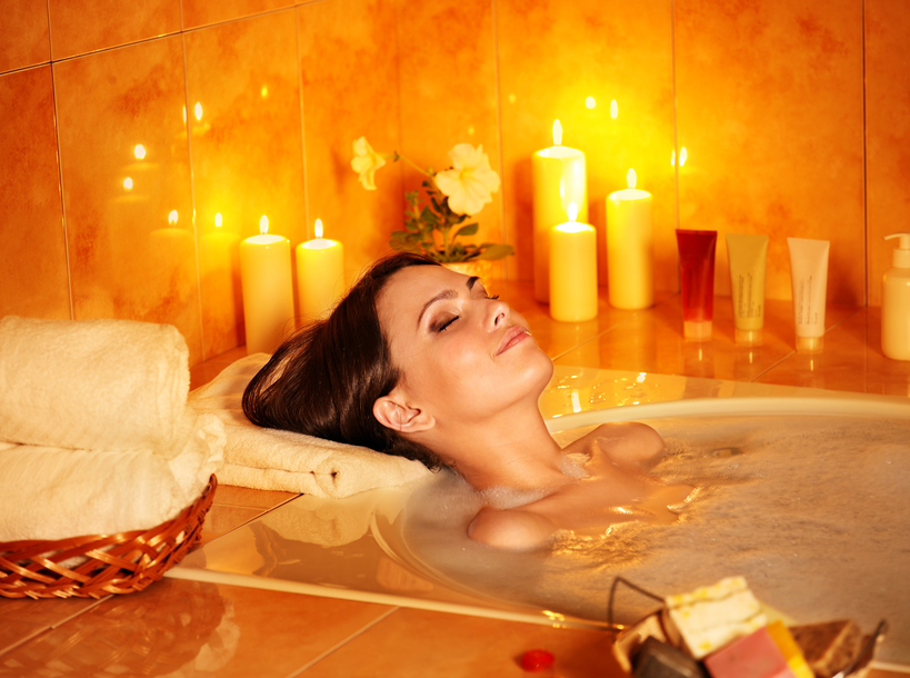 Woman taking a bath in candlelit bathtub