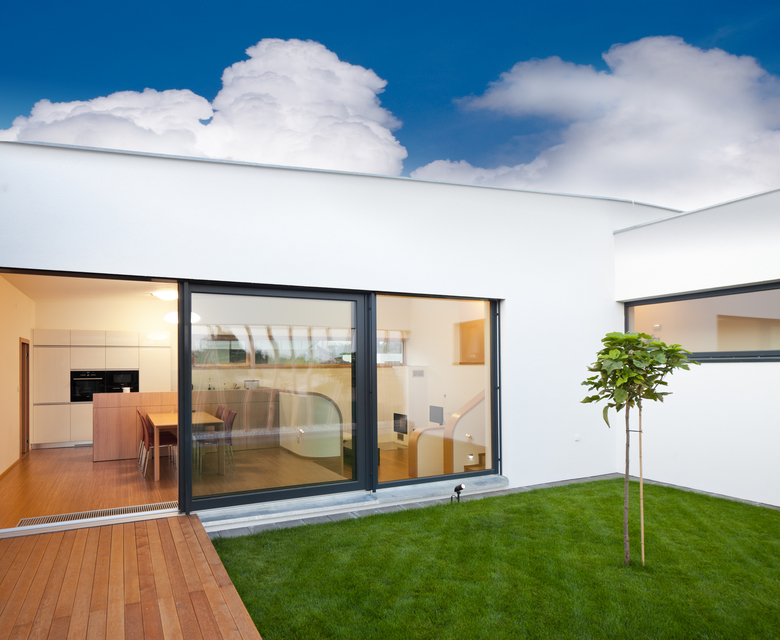 Looking inside home through floor to ceiling windows from courtyard