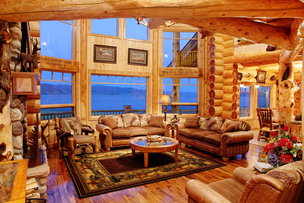 Large family room in log home with exposed logs and rock and brown leather furniture