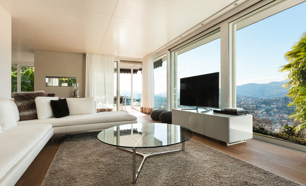 Minimalist family room with 2 white sofas, floor-to-ceiling windows and glass coffee table